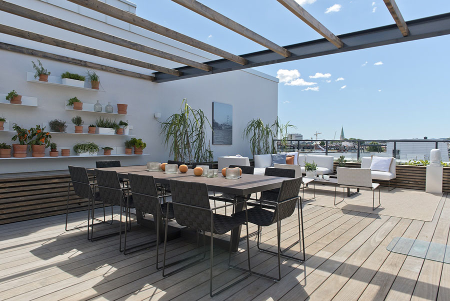 The Secret Rooftop Garden in Kristiansand, Norway with  Kebony Clear Real Wood Decking.  Large potted plants on the deck and small potted plants on wall shelves.