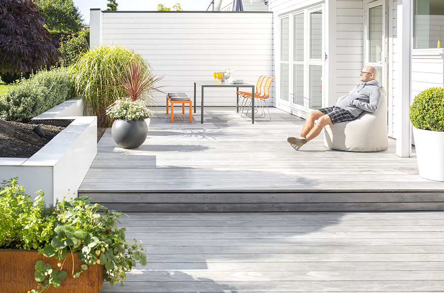 Kebony real wood decking in Clear grade featured in this deck designed by Ronny Kyllingstad. The silver gray color shows the patina the wood develops over time.  In this photo we see a man sitting on his deck, surrounded by potted plants, next to his orange patio furniture.